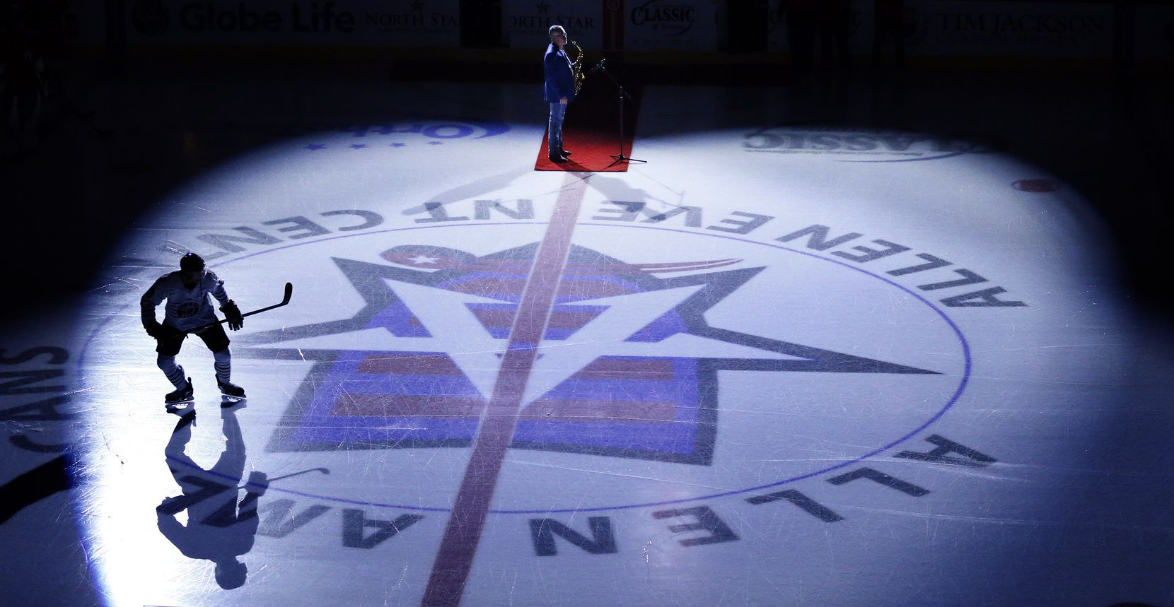 A Rapid City Rush hockey player takes the ice under the spotlights as a saxophonist prepares for the national anthem before the Allen Americans game  at the Allen Event Center in Allen, Texas, Friday, December 18, 2020. This is the first professional hockey game in the metroplex since March. (Tom Fox/The Dallas Morning News)