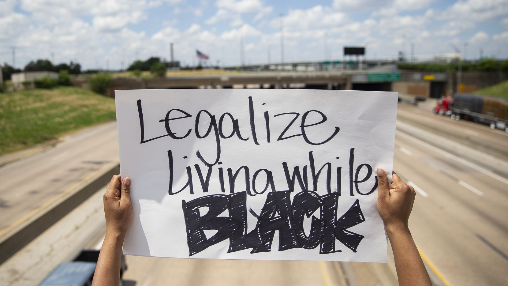 A protestor with the National Injustice Peaceful Rally holds a sign over the E R L Thornton Fwy as they march against police brutality and the recent police killings of George Floyd and Breonna Taylor in Dallas on Sunday, June 7, 2020.