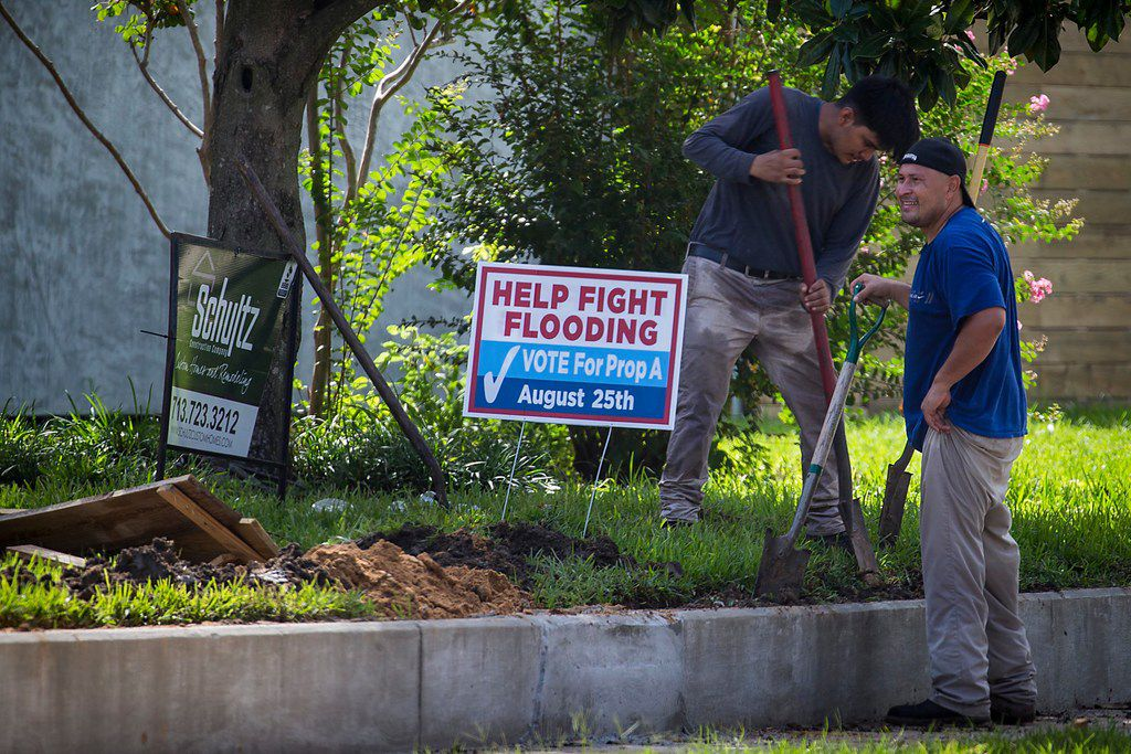 Landscapers work near a sign expressing support for Propsition A, a bond measure that would provide $2.5 billion for flood mitigation, in the Meyerland neighborhood on Saturday, Aug. 11, 2018, in Houston. (Smiley N. Pool/The Dallas Morning News)