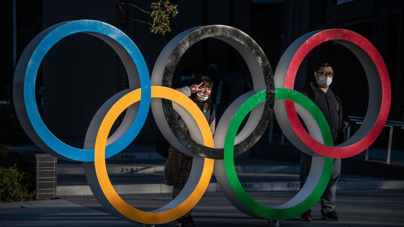 Personas con cubrebocas posan junto a los aros olímpico en Tokio, Japón.