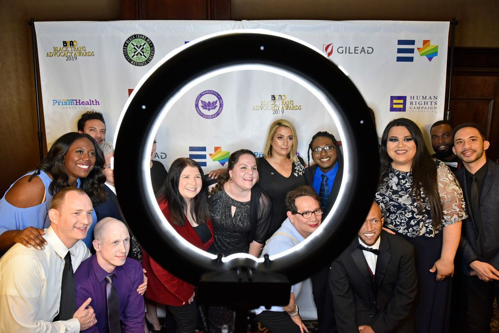 Volunteers with DFW Human Rights Campaign, including Stephanie Lopez, of Denton, left, (in ring light), Cozette Kosary, of Carrollton, and Michelle Lopez, bottom-right (wearing glasses) are photographed on the red carpet at the start of the eighth annual Black Trans Advocacy Conference and awards gala at the Wyndham Suites Hotel in Dallas, Friday April 26, 2019.