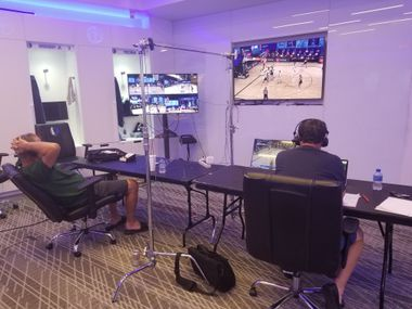 The Dallas Mavericks radio broadcast team of Chuck Cooperstein (right) and Brad Davis are calling games for ESPN 103.3 from the team's locker room at American Airlines Center in Dallas.  Cooperstein, who handles play-by-play and analyst Davis each work on separate long tables facing an 80-inch TV screen on the wall.