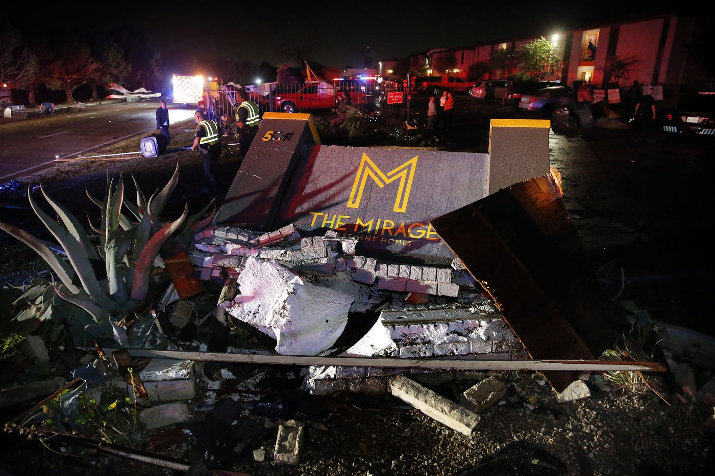 The Mirage Apartments sign lies damaged along Pioneer Parkway in Arlington following a tornado-warned storm, Tuesday night, November 24, 2020. Apartment building roofs, air conditioner units and other structural debris were scattered across the property and the street.  (Tom Fox/The Dallas Morning News)