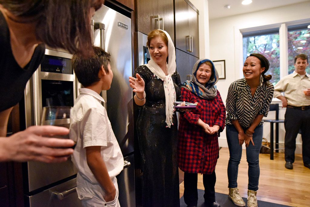 Jamileh Jafari jokes with her son Michael Jafari, left, after she cooked an Afghan style dinner for the Sunday Supper Series in Dallas on April 2. At right of Jafari is her sister Sharifeh Hasani and Kim Simithraaratchy. The supper series is organized by Olga Pope and Simithraaratchy to raise funds for refugee families.