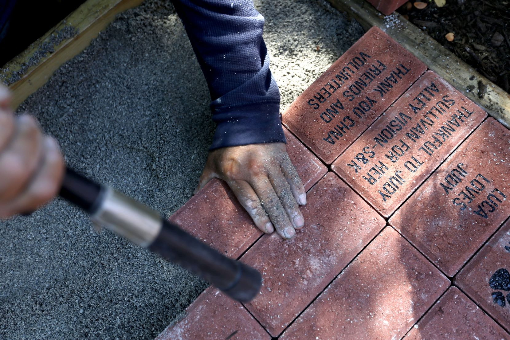 Alex Lira works to install commemorative engraved bricks that were sold to raise funds for the project.