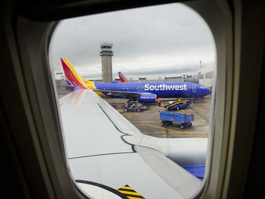 A Southwest Airlines 737-700 sits at an adjacent gate  at Dallas Love Field as seen from a passenger seat of a flight about to depart for Houston on Friday, March 20, 2020, in Dallas.