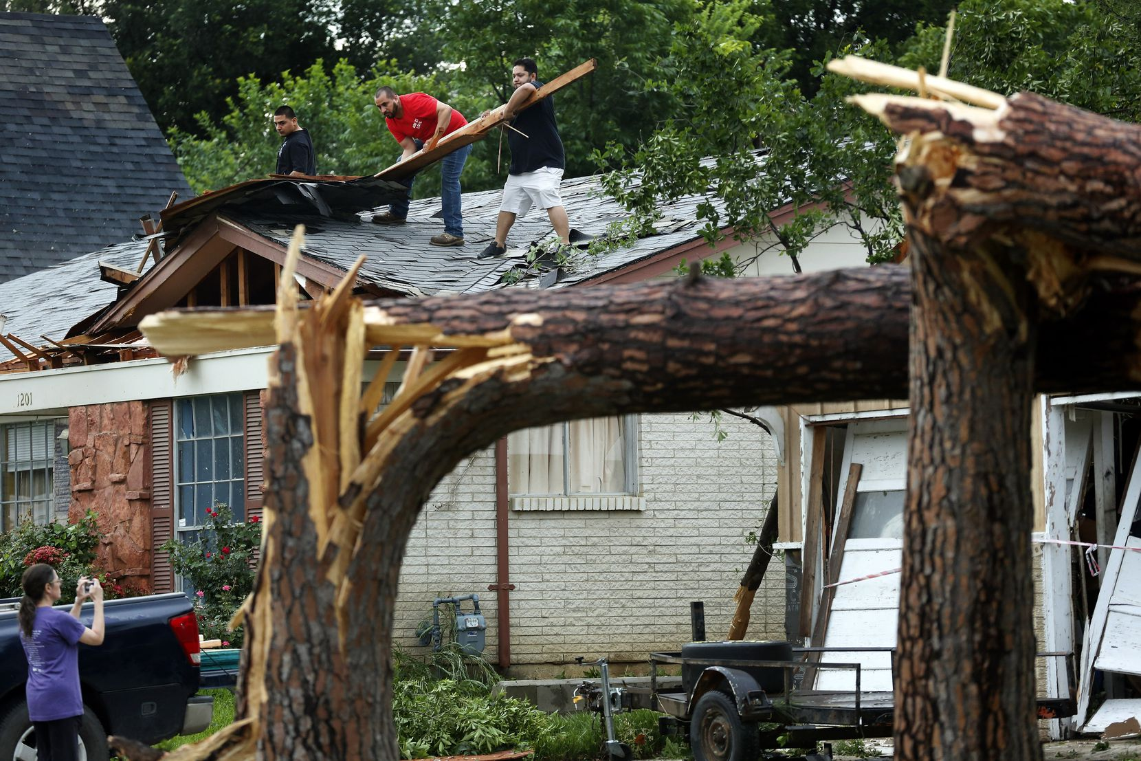Volunteers help residents along Andrews St. clear roof debris in north Arlington after large trees were toppled Sunday.
