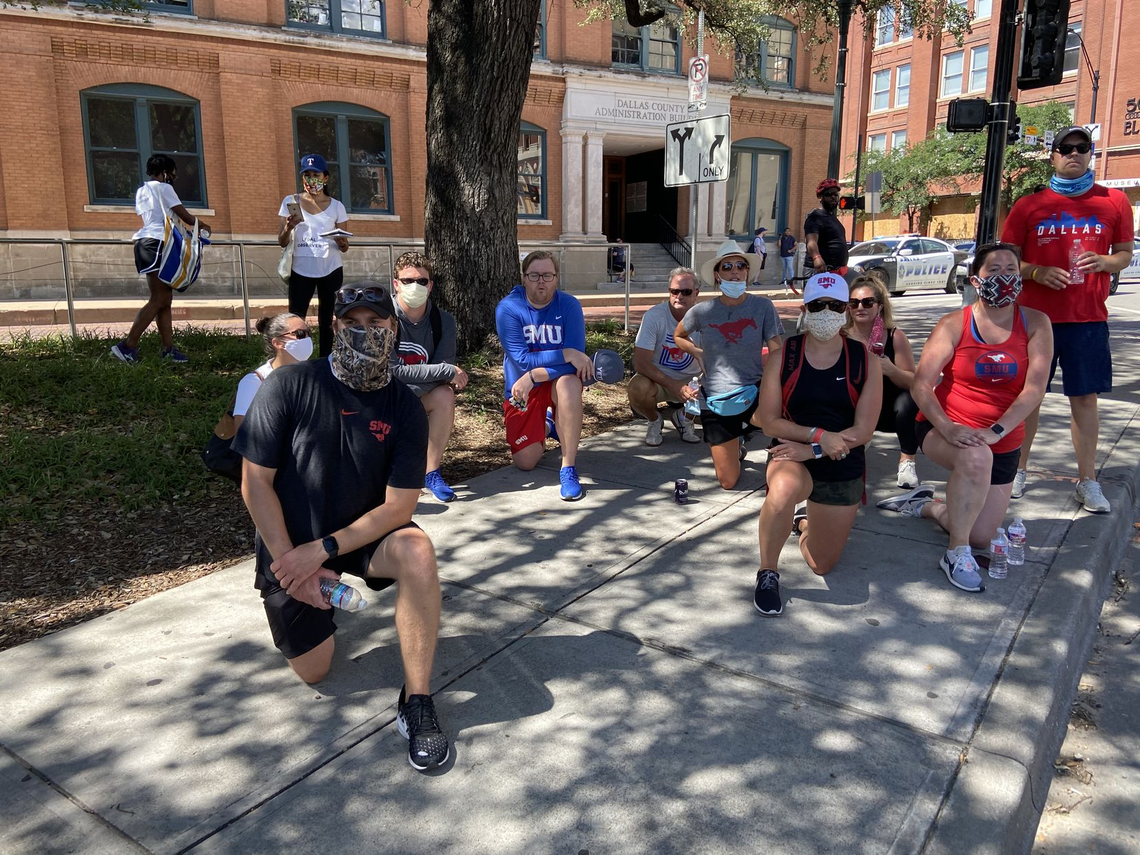 SMU staff members kneel in support of protesters near Dealey Plaza on June 5, 2020. (By Sam Blum.)