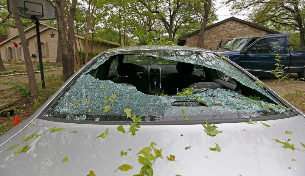 A car damaged by last night's hailstorm sits in a driveway on Tangle Wood Lane in Highland Village, Texas, Monday, March 27, 2017. (Jae S. Lee/The Dallas Morning News)