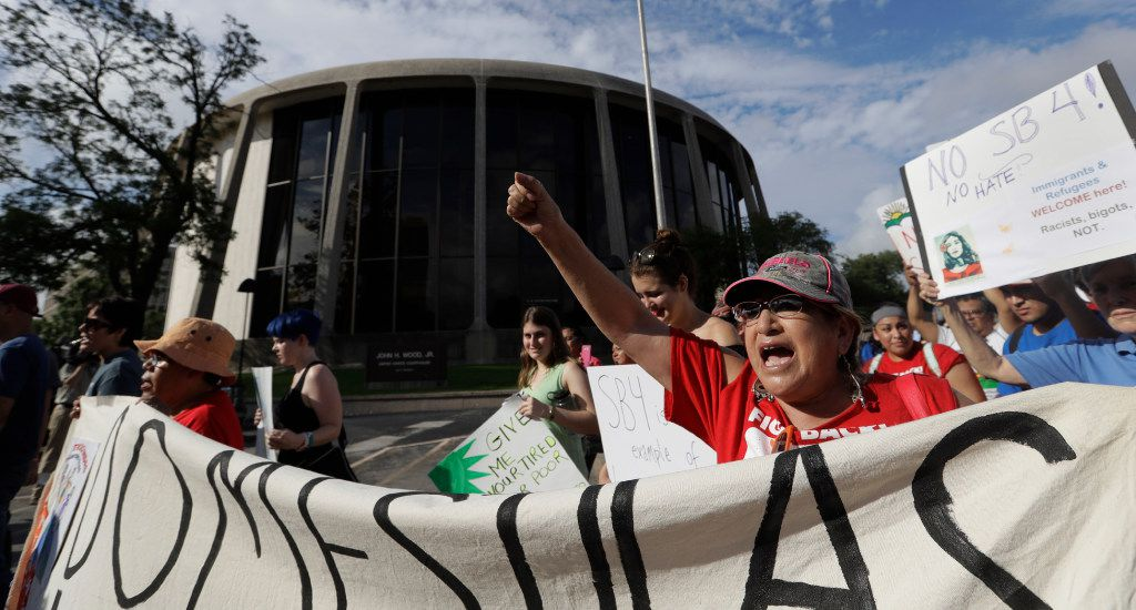 "Protesters march outside the Federal Courthouse to oppose a new Texas ""sanctuary cities"" bill that aligns with the president's tougher stance on illegal immigration, Monday, June 26, 2017, in San Antonio. (AP Photo/Eric Gay)"