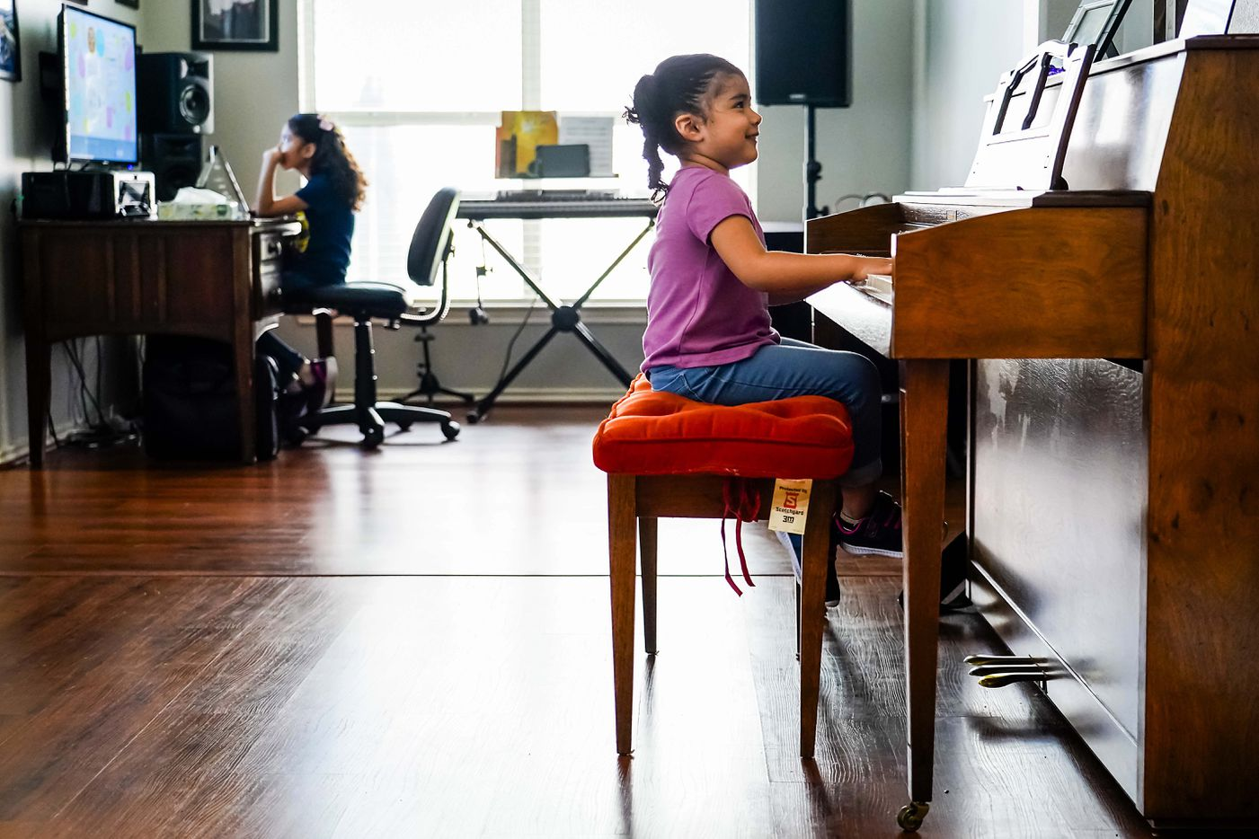 Kamila Cabrera, 4, plays the piano as her sister Selena Cabrera, 9, does school work on a computer at the family's home in Grand Prairie.