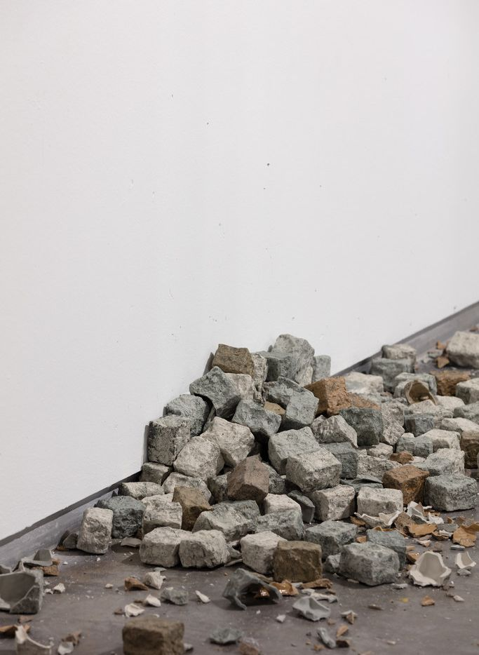 Alicja Kwade's TonSteineScherben features cobblestones, representative of violent May Day clashes, that have been thrown against the wall, broken to pieces and collected in a pile on the floor.