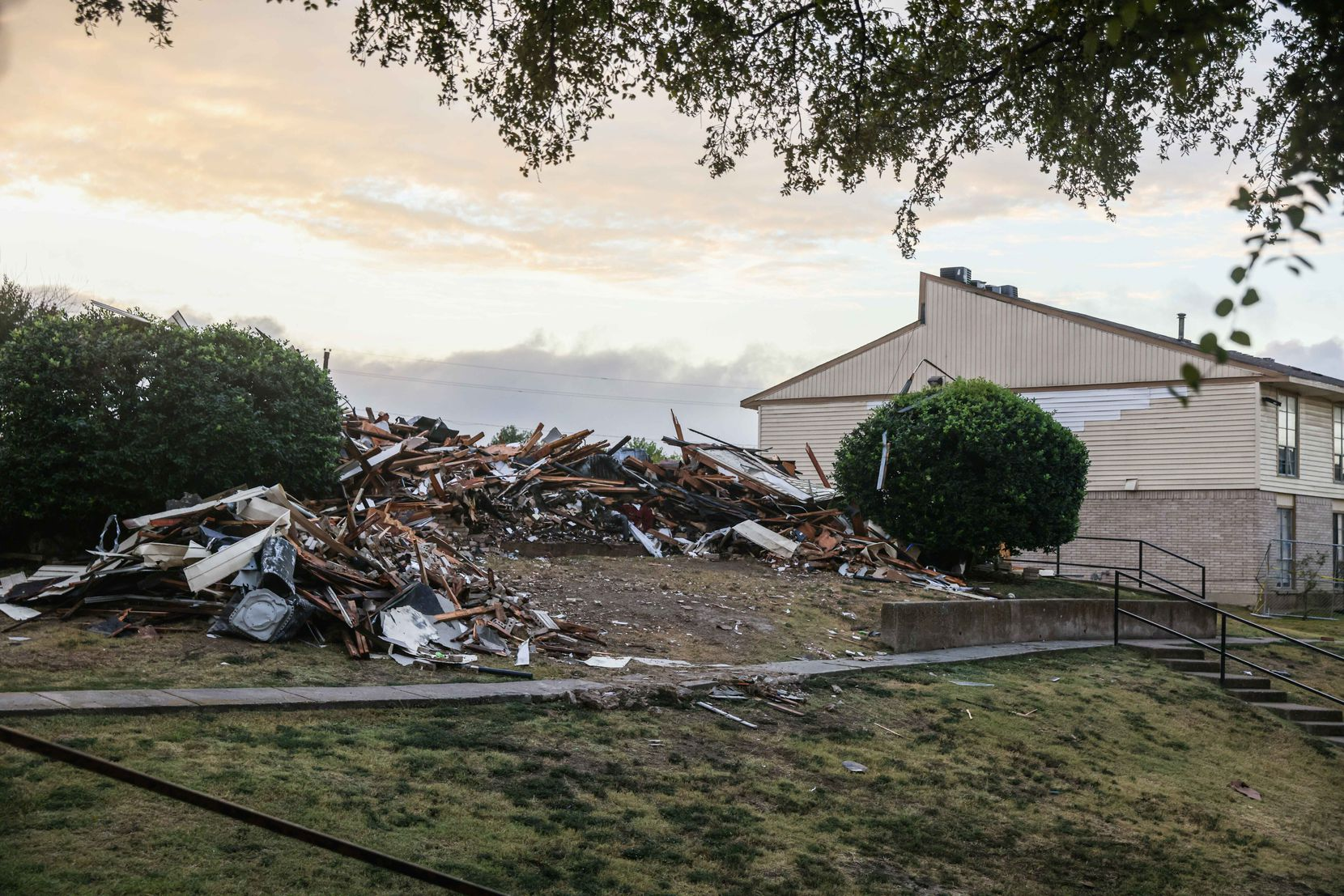 Rubble from Wednesday's explosion at the Highland Hills Apartments and the subsequent razing of the building that blew up has been heaped into piles at the complex.