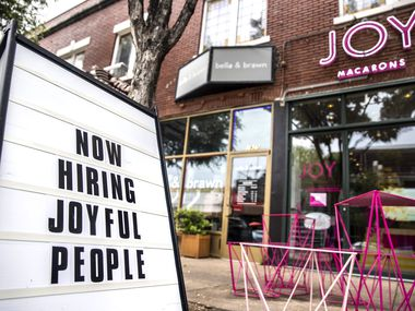 """A """"Now Hiring"""" sign stood outside JOY Macarons in Dallas earlier this summer."""
