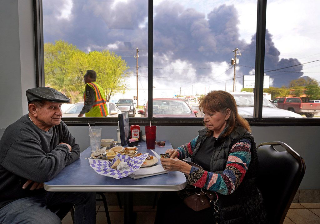 Charlie Tamez and his wife, Dalia Tamez, finish their lunch at Ken's Restaurant, 1122 Center St., as the chemical fire at Intercontinental Terminals Company continues to send dark smoke over Deer Park, Texas, Tuesday, March 19, 2019.