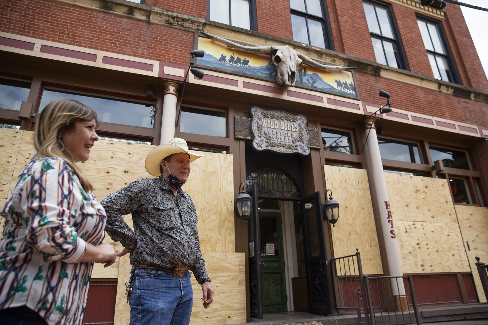 Wild Bill's Western Store managers Cynthia Meneses and Bruce Bean chatted outside the West End store on Monday. Its windows were broken during the protests despite a 7-foot-high plywood barrier.