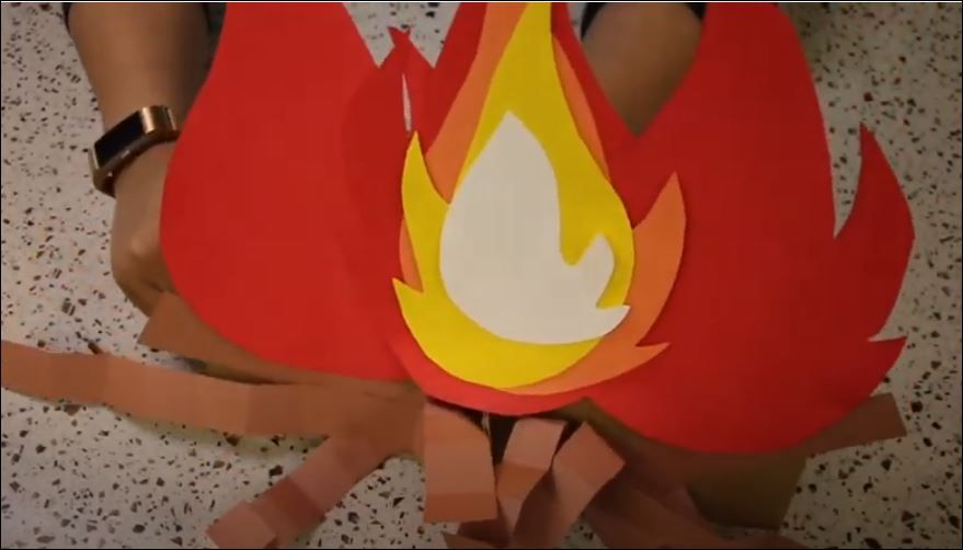 As a substitute for a real campfire, a counselor working for the Dallas Parks & Recreation Department's virtual summer camp shows how to make a faux fire out of construction paper.