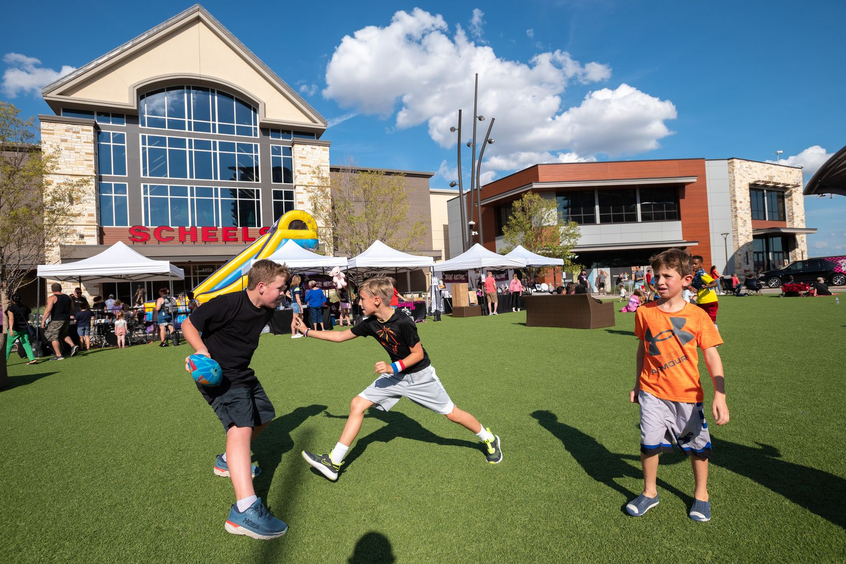 Thatcher Jones, left, and Zach Maris, center, play a game of 2 vs 2 man football on the green turf at Grandscape in The Colony.