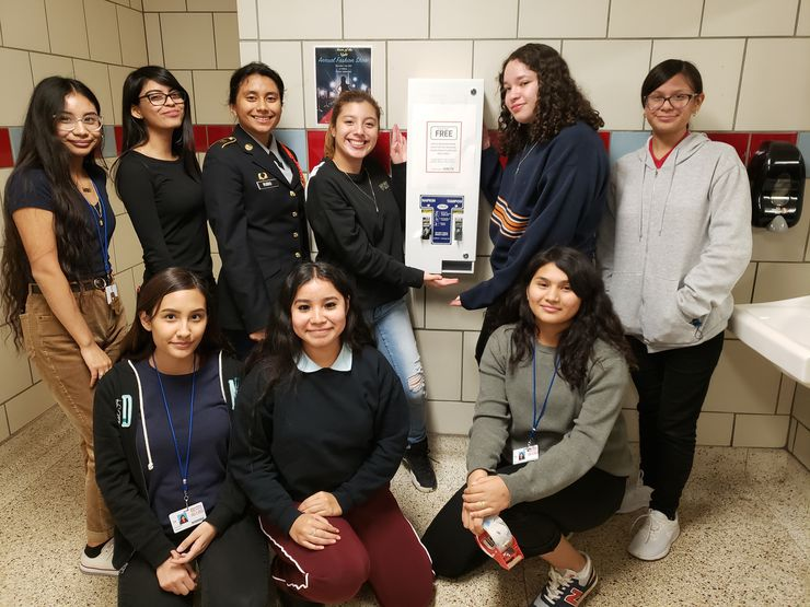 Members of Skyline High School's IGNITE club celebrate the installation of a feminine hygiene product dispenser in their high school bathroom.