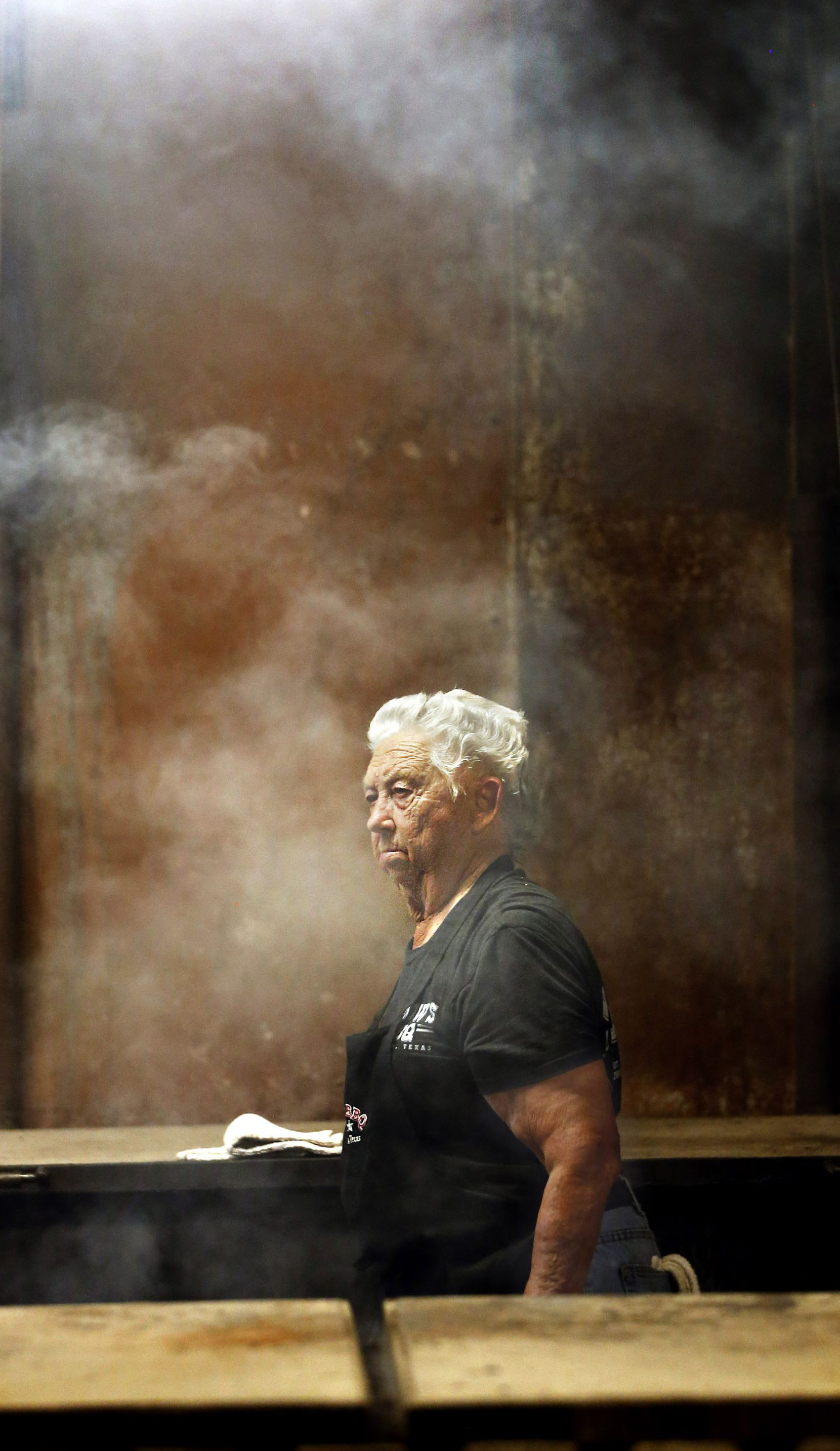 Tootsie Tomanetz makes her way between barbecue pits at Snow's BBQ. She  begins work at 2 a.m. on Saturdays.