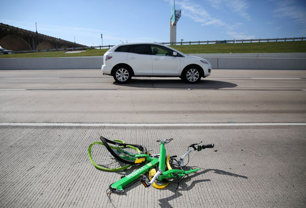 The mangled remains of a LimeBike rental bike lie alongside I-35E in downtown Dallas on Nov. 11, 2017.