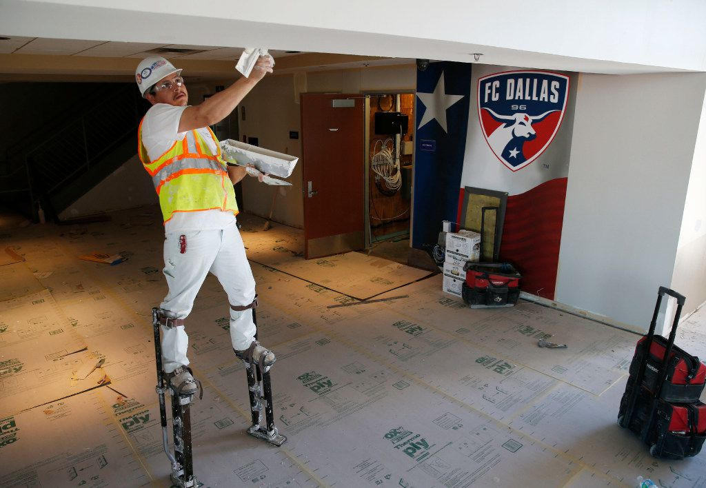 Juan Olivas works on finishing up the drywall in the Winners Club area at Toyota Stadium in Frisco on Thursday.