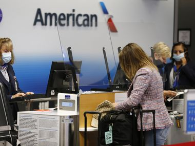 An American Airlines agent tends to customers in Terminal C at DFW International Airport on Tuesday, July 21, 2020.
