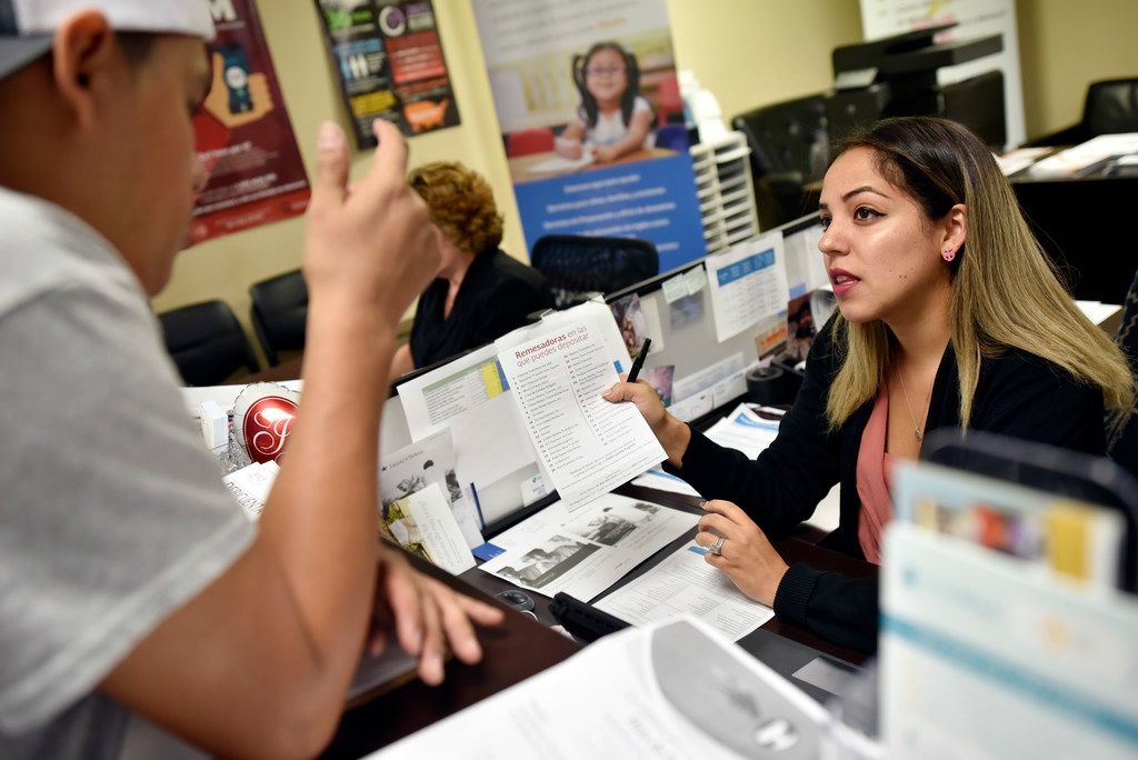 Jasmine Bueno, a financial coach with Catholic Charities, speaks with a Mexican immigrant as he seeks financial advice at the information window inside the Mexican Consulate in Dallas.