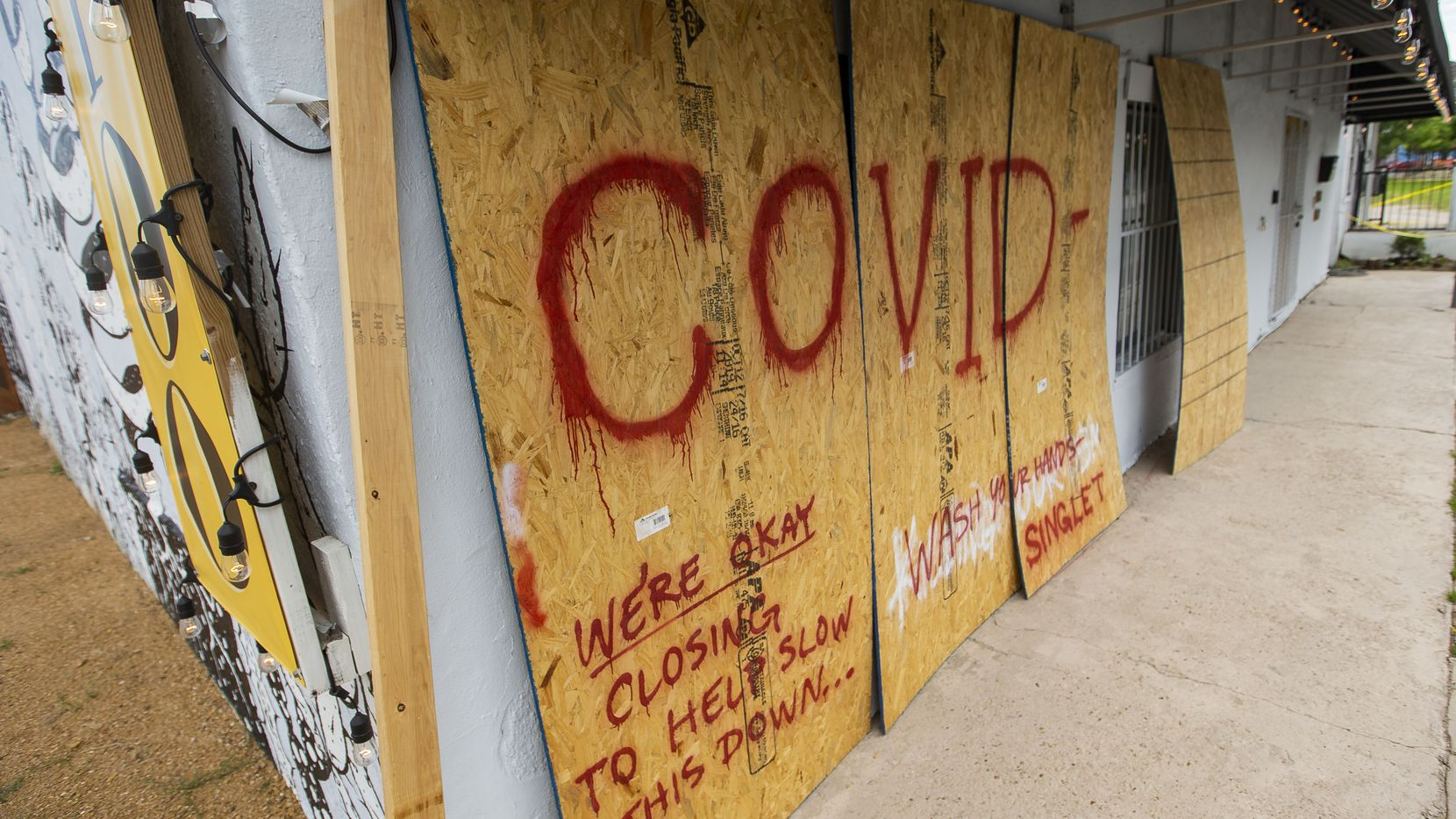 Boarded up windows at Singleton Tattoo, which is closed because of the coronavirus outbreak, on April 18, 2020 in Dallas.
