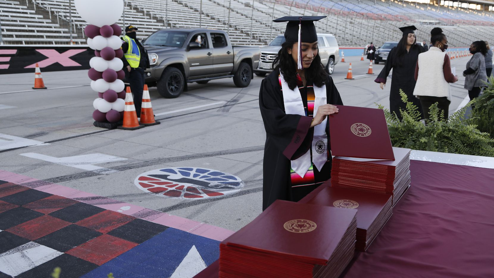 Michelle Castro picks up her diploma cover at the finish line as Texas Woman's University held their graduation ceremony at the Texas Motor Speedway in Fort Worth on Dec. 12, 2020.