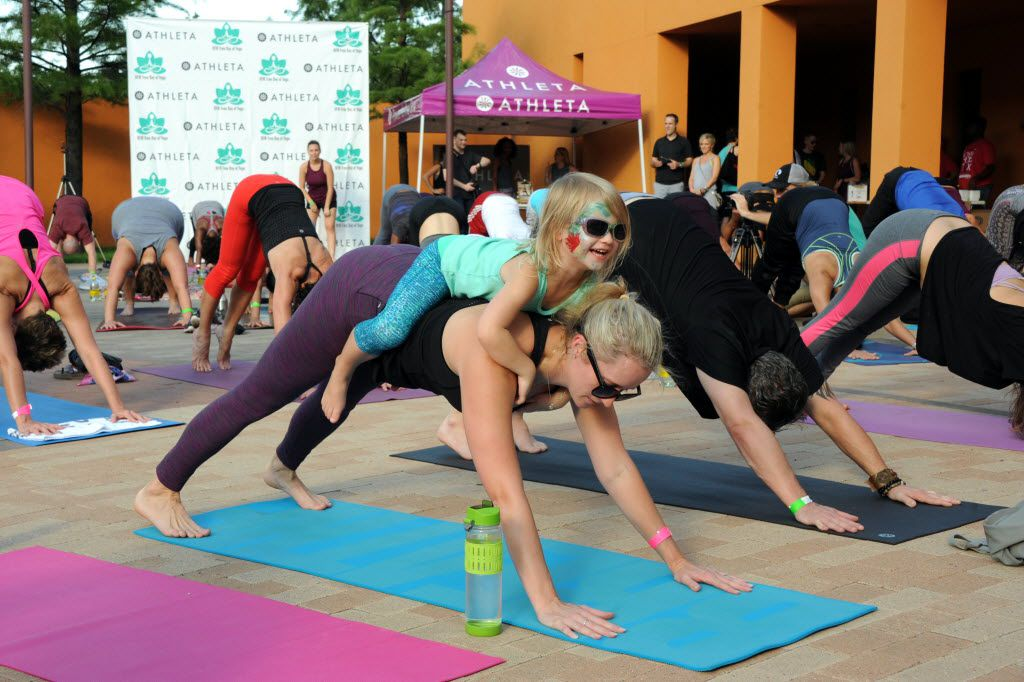 Mother and daughter practice downward-facing dog at the D-FW Free Day of Yoga Kickoff at the Latino Cultural Center in Dallas, TX on September 3, 2016. (Alexandra Olivia/ Special Contributor)