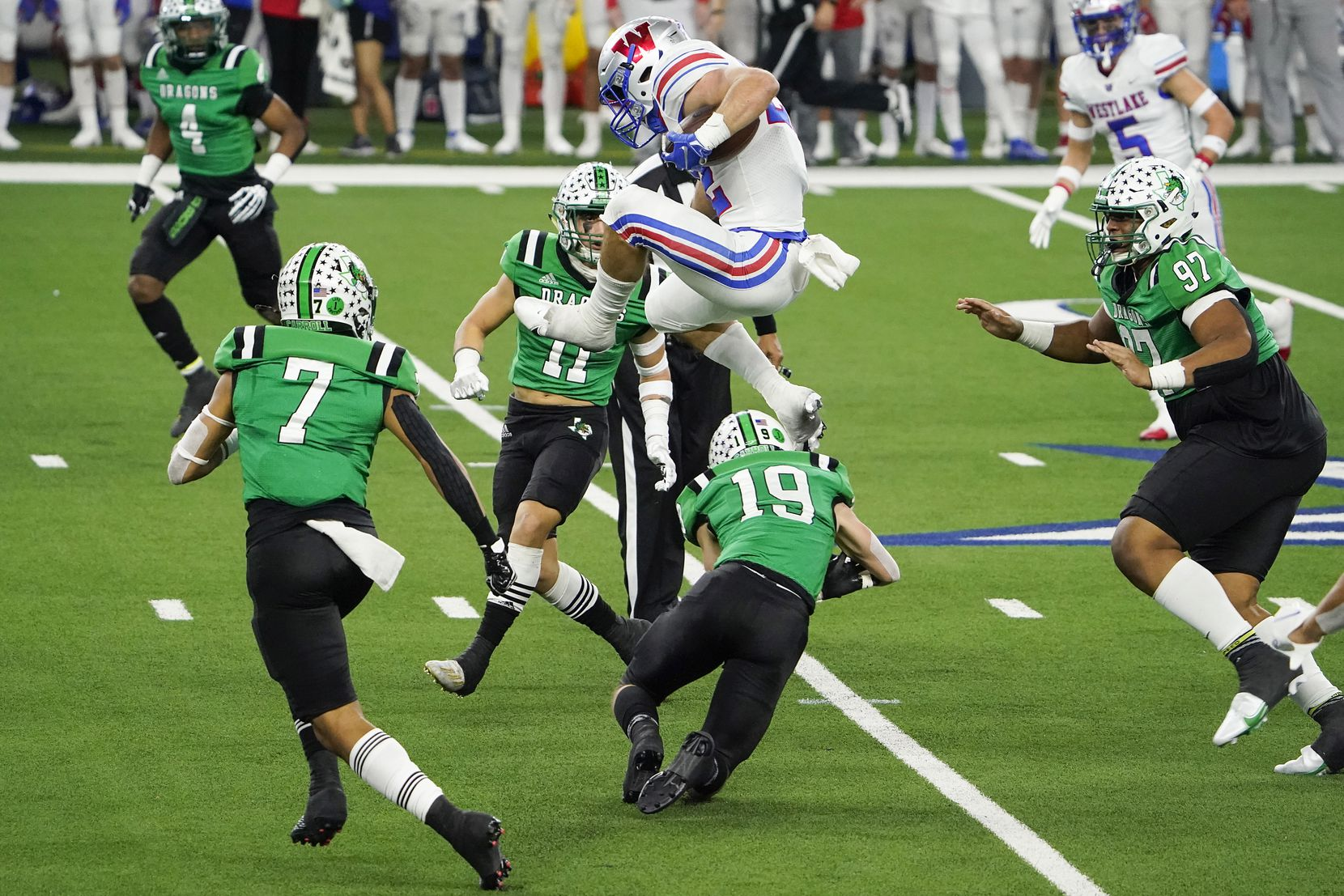 Austin Westlake running back Grey Nakfoor (22) hurdles Southlake Carroll defensive back Logan Anderson (19) on a run during the third quarter of the Class 6A Division I state football championship game at AT&T Stadium on Saturday, Jan. 16, 2021, in Arlington, Texas.