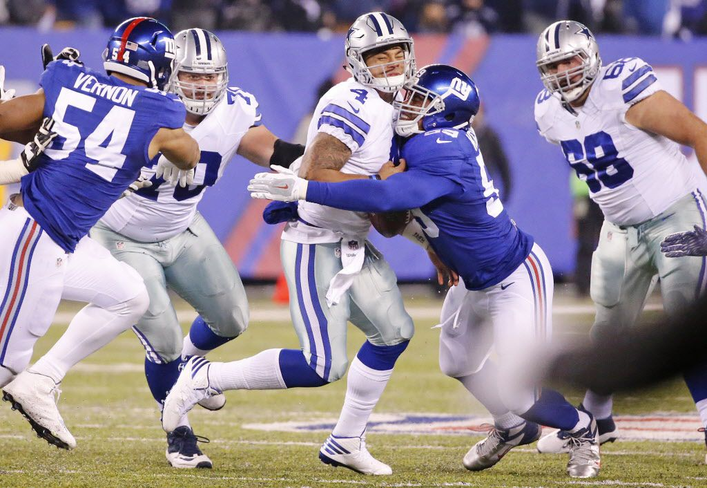Dallas Cowboys quarterback Dak Prescott (4) fumbles as he is hit by New York Giants nose tackle Robert Thomas (99) in the second quarter during the Dallas Cowboys vs. the New York Giants NFL football game at MetLife Stadium in East Rutherford, New Jersey on Sunday, December 11, 2016. (Louis DeLuca/The Dallas Morning News)