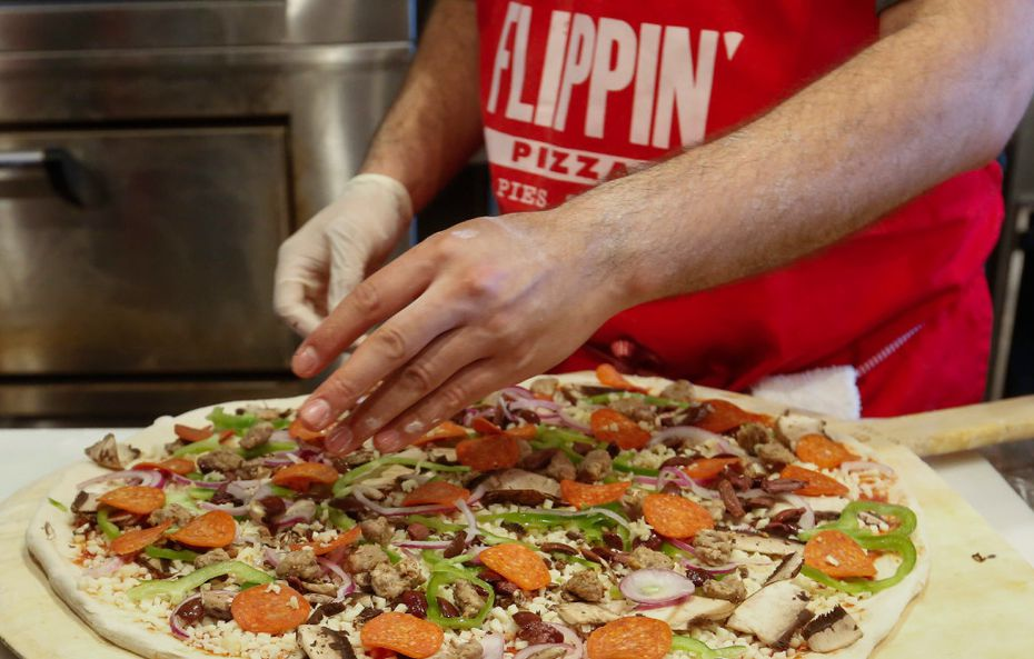 Carlos Osuna puts the finishing touches on a 18-inch pizza at Flippin' Pizza.