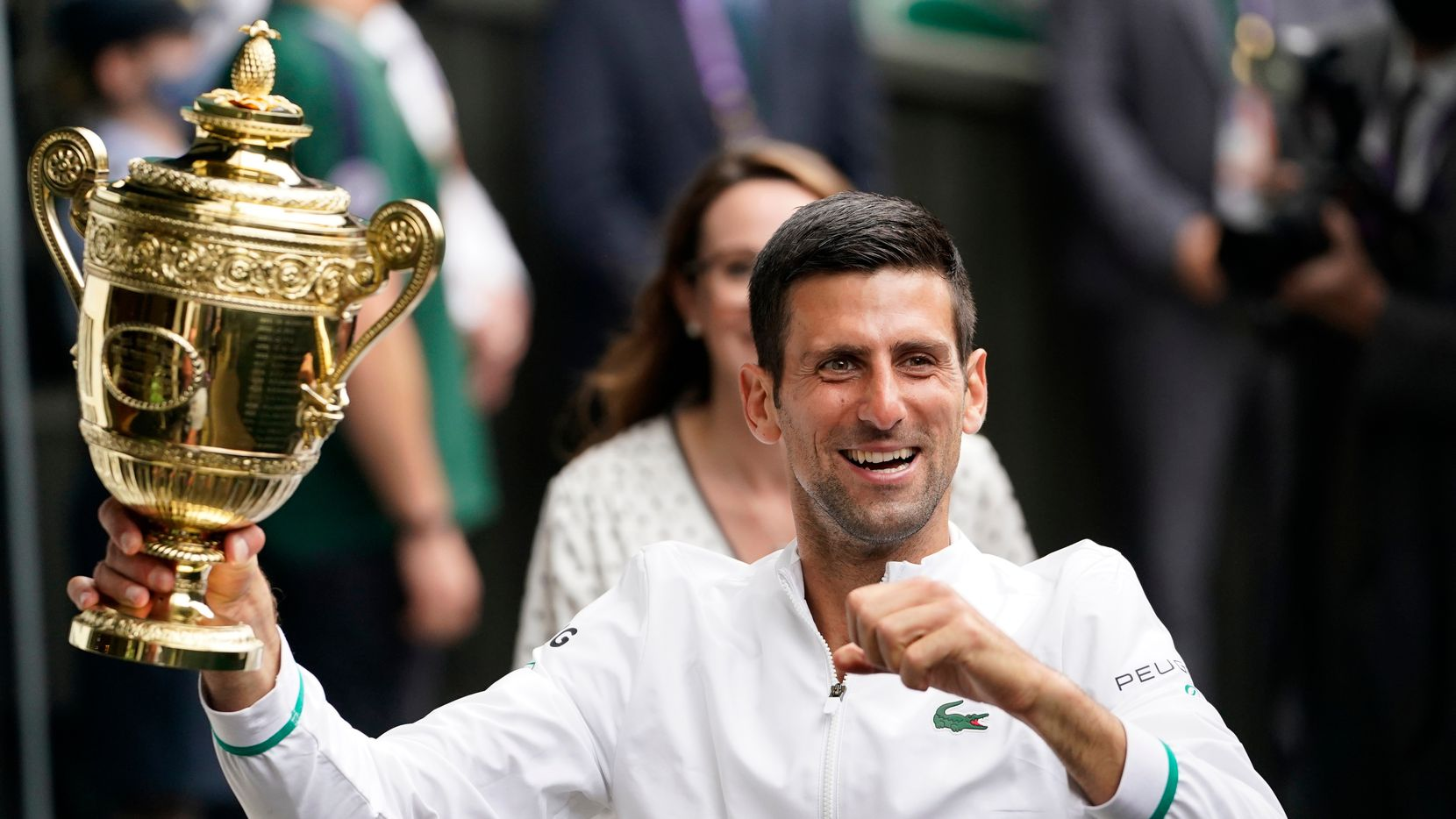 Serbia's Novak Djokovic holds the winner's trophy after his victory over Italy's Matteo Berrettini during the men's singles final match on day thirteen of the Wimbledon Tennis Championships in London, Sunday, July 11, 2021. (AP Photo/Alberto Pezzali)
