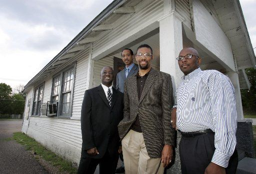(Left to Right) Jai Poole, Tony Owens, Pastor Vincent Parker and Obie Bussey pose together outside the old Adult Rehabilitation Ministry (ARM) Building at the Golden Gate Missionary Baptist Church in Dallas. The old building was razed to make way for a new, larger one for the growing ministry.