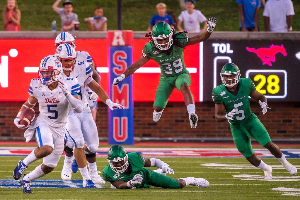 SMU running back Xavier Jones (5) breaks through the UNT defense of defensive back Taylor Robinson (24), defensive back Jameel Moore (39) and linebacker Tyreke Davis (5) during the first half of an NCAA football game at Ford Stadium on Saturday, Sept. 7, 2019, in Dallas. (Smiley N. Pool/The Dallas Morning News)