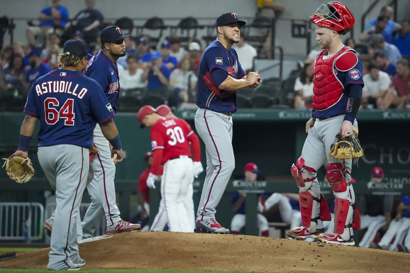 Minnesota Twins starting pitcher Jose Berrios gets a visit from catcher Ryan Jeffers after walking Texas Rangers first baseman Nate Lowe (30) during the second inning at Globe Life Field on Friday, June 18, 2021.