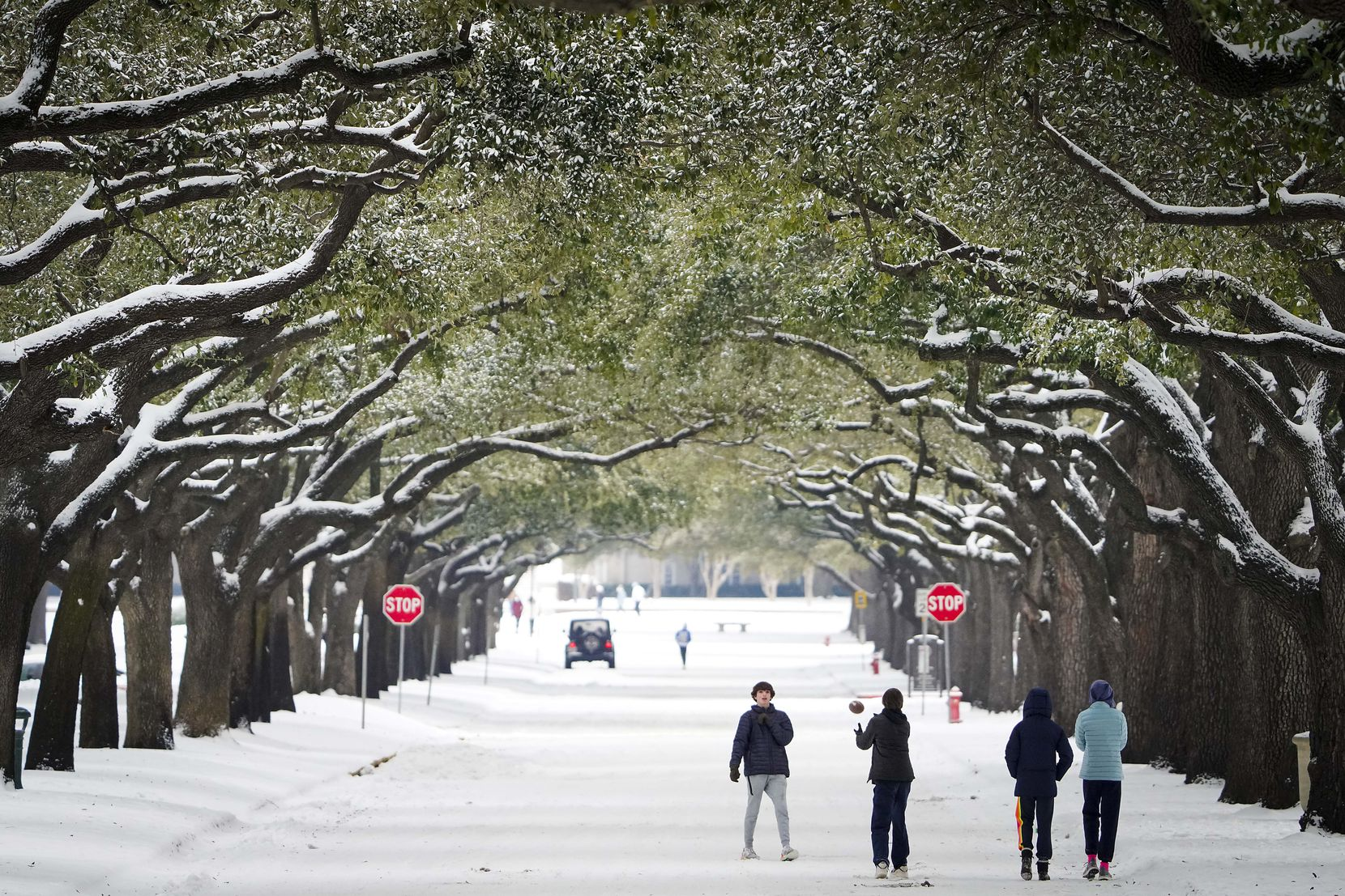People toss a football on Bishop Boulevard on the SMU campus after a second winter storm brought more snow and continued freezing temperatures to North Texas on Wednesday, Feb. 17, 2021, in Dallas.