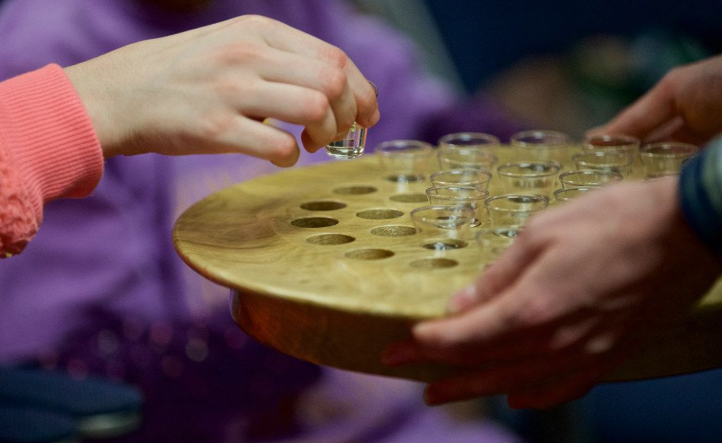 """Jacob Smith, right, offers juice to Margaret Laceky during communion during """"The Feast"""" church service for people with special needs at Highland Park United Methodist Church on Sunday, January 8, 2017."""