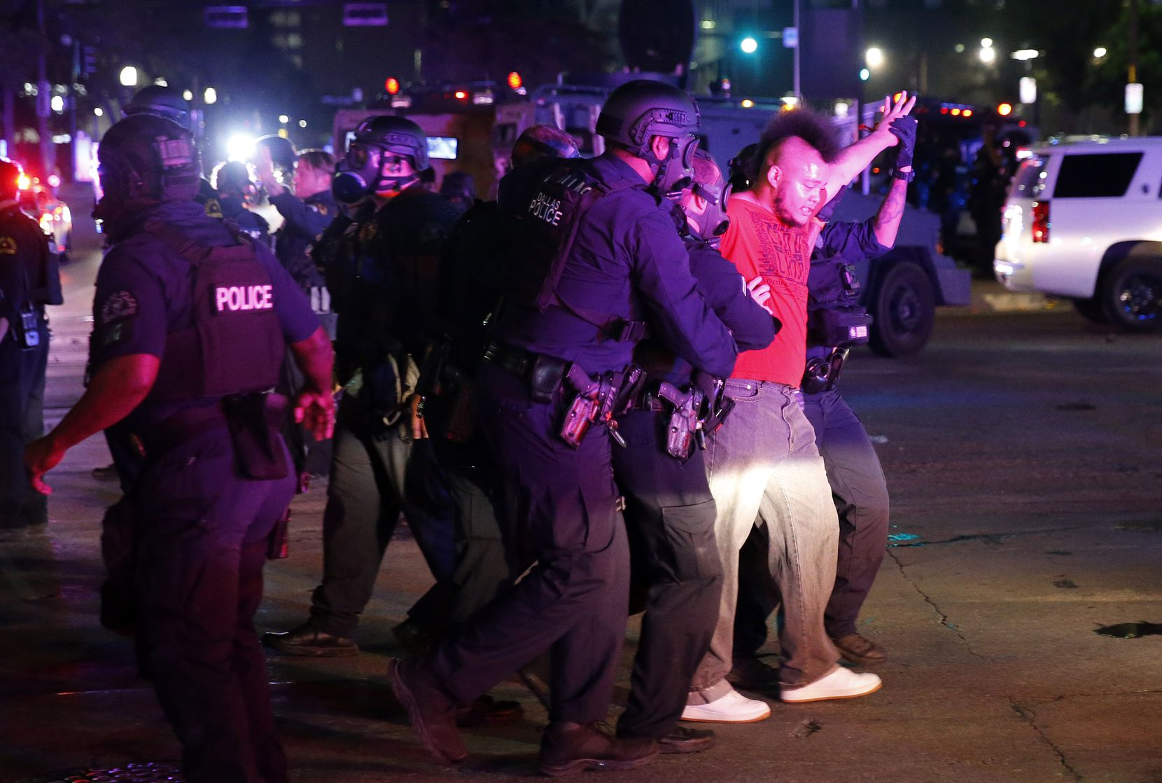 A protestor is taken into custody by Dallas Police tactical officers at Young St. and S. Griffin St. in downtown Dallas, Friday, May 29 2020. People were marching in protest of the in-custody death of George Floyd when they confronted Dallas Police tactical officers and tear gas was fired.