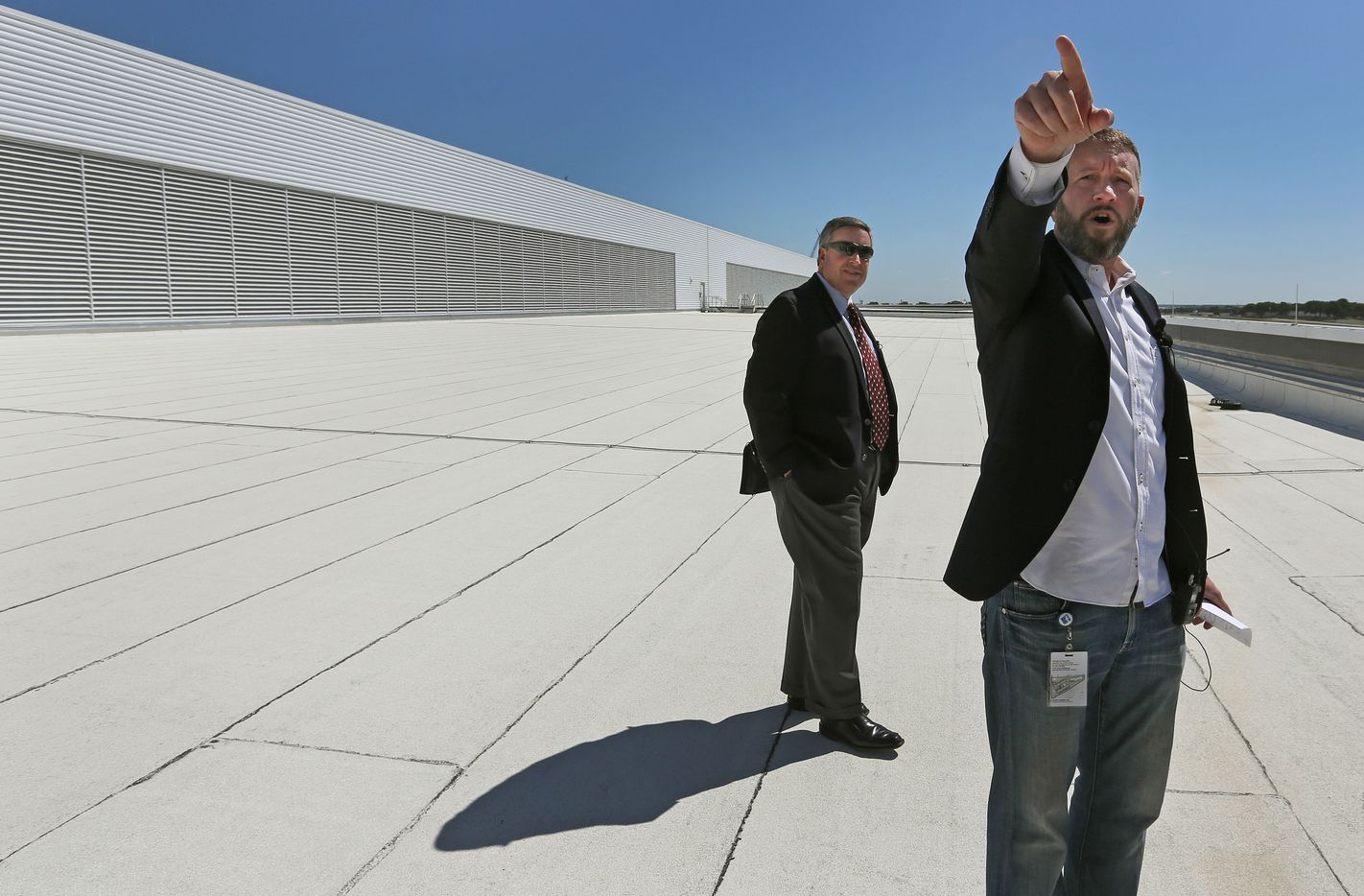 Site Manager KC Timmons, right, and Tom Furlong, Vice President of Infrastructure at Facebook, point out the massive size of the facility from the roof during the grand opening and tour of Facebook's Fort Worth Data Center.