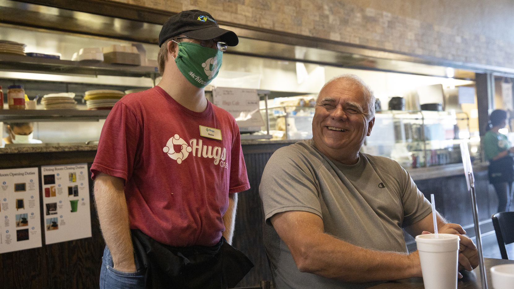 "Blaine Hardin (left) chats with Hugs Café co-founder Chris Thompson and his family at the McKinney eatery. Hardin is one of the café's employees, or ""teammates."" Hugs is one of many McKinney non-profits accepting donations as part of North Texas Giving Day."