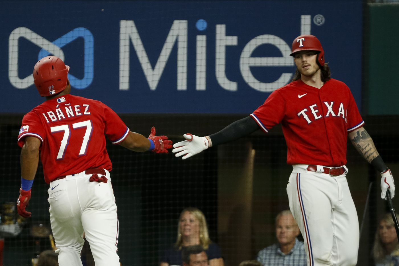 Texas Rangers designated hitter Andy Ibanez (77) high-fives Texas Rangers catcher Jonah Heim (28) after scoring a run during the sixth inning against the Kansas City Royals at Globe Life Field on Friday, June 25, 2021, in Arlington. (Elias Valverde II/The Dallas Morning News)