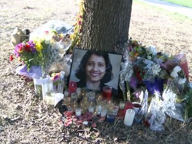 Flowers and candles surround a photo of 43-year-old Sarmistha Sen on Aug. 8. Sen was found slain Aug. 1 near a creek in Plano, police said.