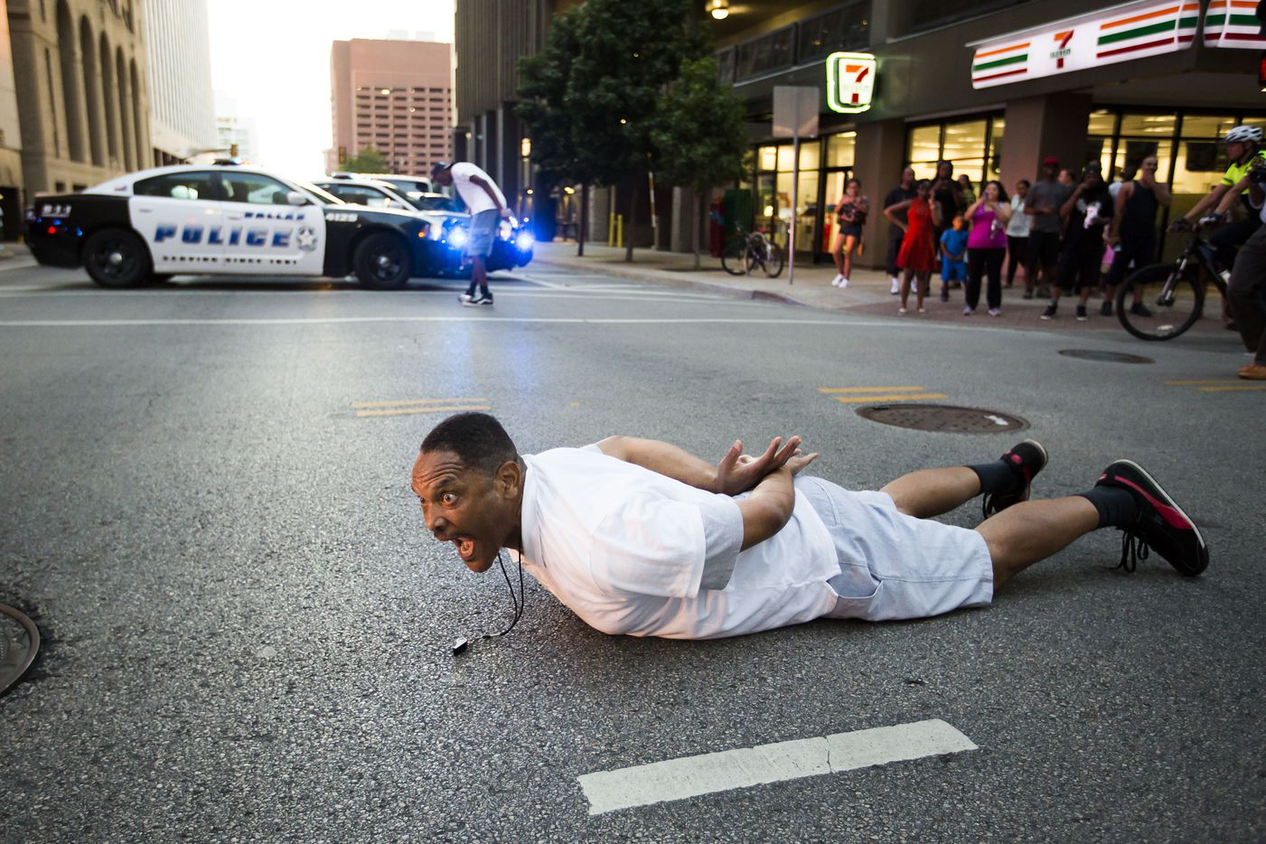 A protester who identified himself as Keng lies down in the middle of the intersection of Commerce and Field streets in front of police during the Black Lives Matter march. (Smiley N. Pool/Staff Photographer)