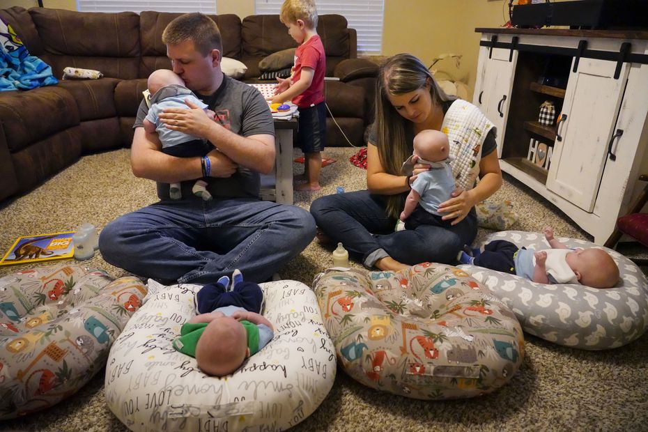 Chris and Katie Sturm fed quadruplets (from left) Jacob, Austin, Daniel and Hudson, who were born in July, at their home as 3-year-old son Ryan plays in the background on Tuesday, Sept. 29, 2020, in Haslet, Texas. (Smiley N. Pool/The Dallas Morning News)