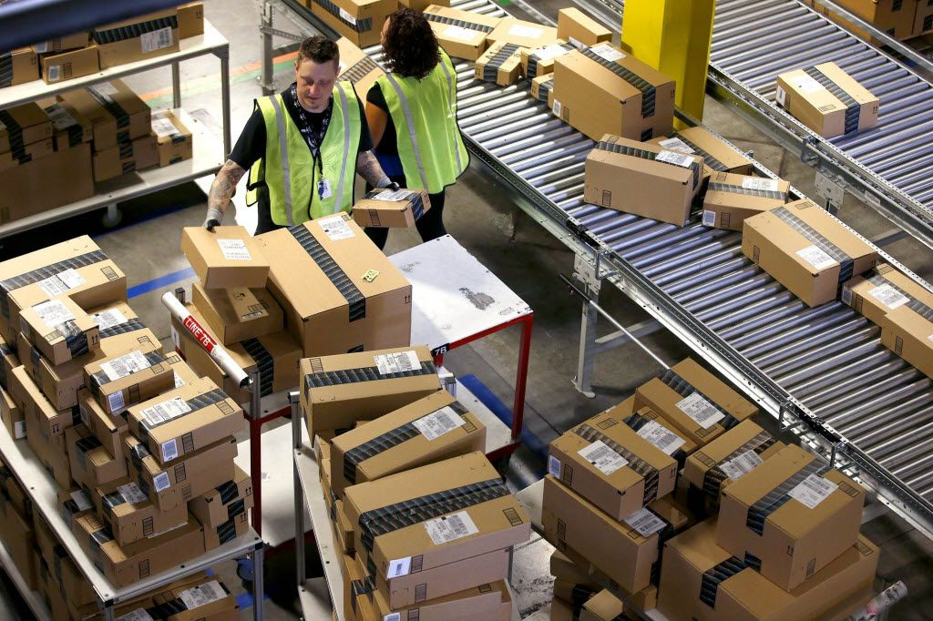 Amazon employees organize outbound packages at a fulfillment center in Phoenix.