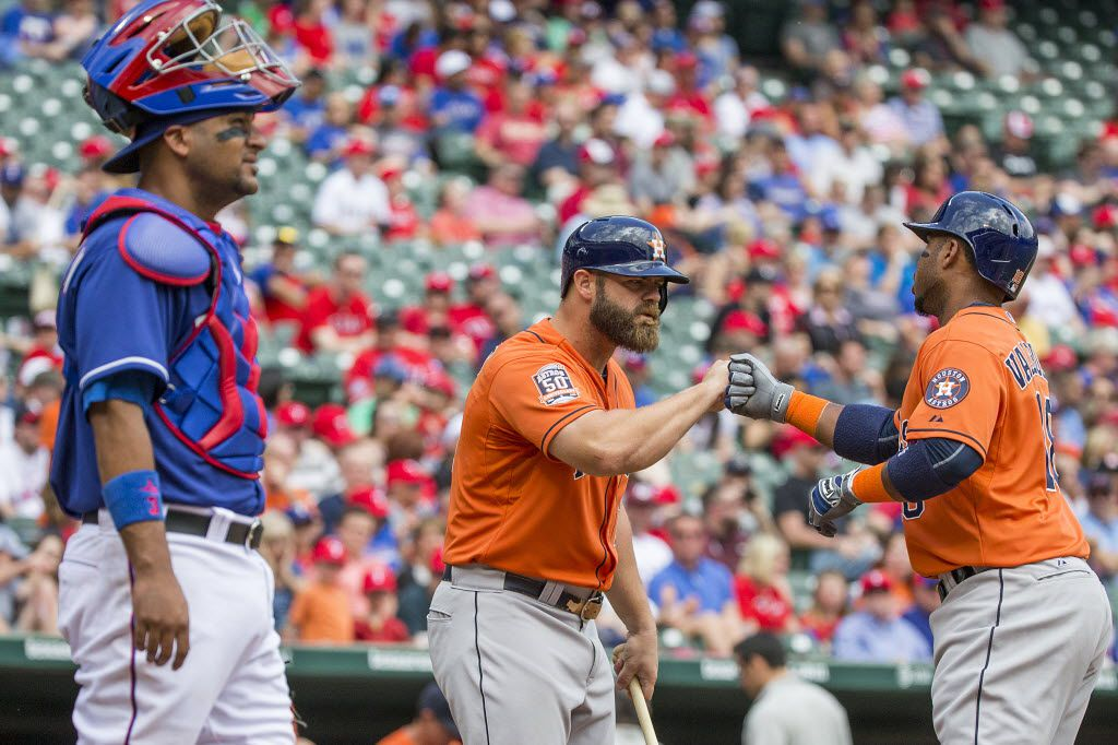 Houston Astros third baseman Luis Valbuena (18) is congratulated by designated hitter Evan Gattis (center) as Texas Rangers catcher Carlos Corporan looks on after hitting a solo home run during the second inning at Globe Life Park on Sunday, April 12, 2015, in Arlington. (Smiley N. Pool/The Dallas Morning News)