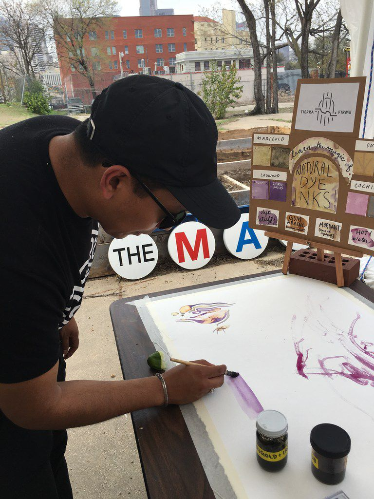 Lucas Martell, an artist, demonstrates how to paint with natural dyes at The MAC POP Garden open house.